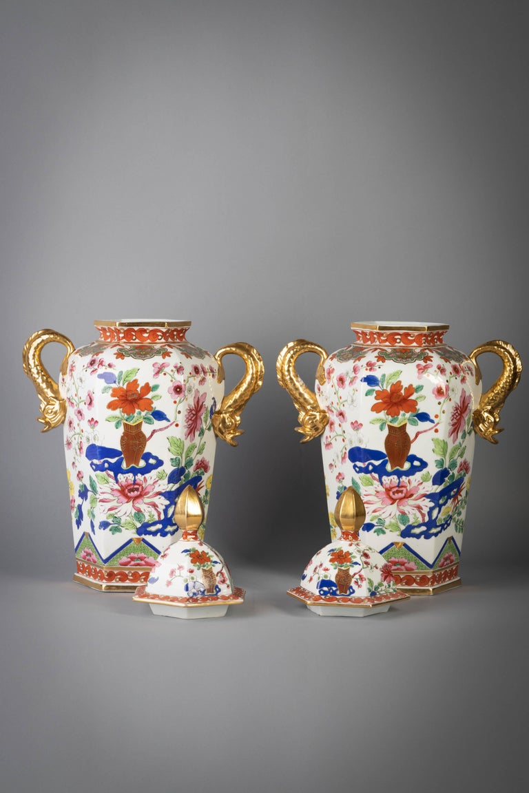 Each of hexagonal form with gilt dolphin handles, painted in the famille rose palette and enriched with blue, the front and back with chrysanthemum issuing from a brown vase and flowering peony and flowering branches, the covers similar decorated