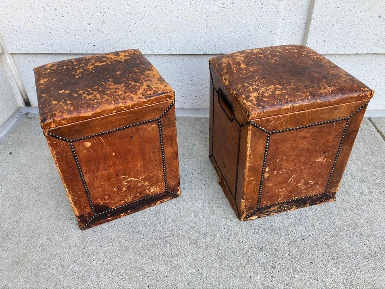 Great pair of leather covered nail head stools with lift tops and cedar interiors. With open handles on the sides for easy lifting. This is a look that only comes with age and use, these were clearly well loved, and well used. They are scuffed up,