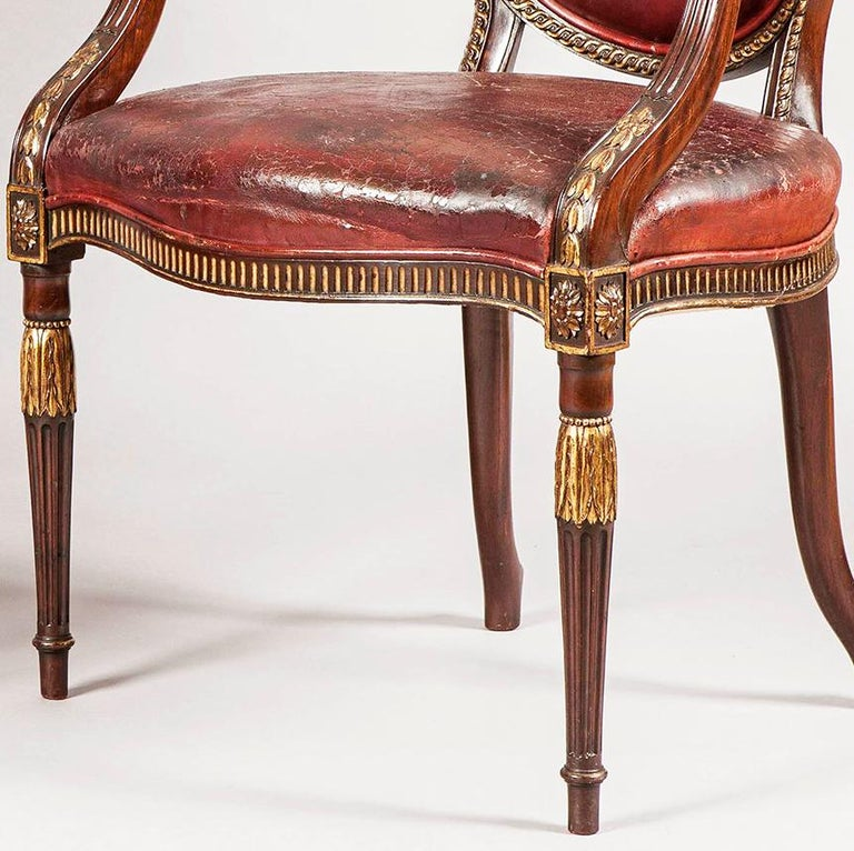 A fine pair of armchairs in the neoclassical in the manner of Robert Adam  Constructed in mahogany with hand-painted gilt accents and red leather, each with oval backs enclosed with interlocking dart and braid carved design, with outswept arms