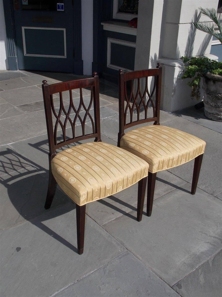 Pair of English mahogany Sheraton side chairs with flanking ball finials, reeded side rails, crosshatching splat backs, upholstered silk striped seats and terminating on the original tapered reeded legs, Early 19th century.