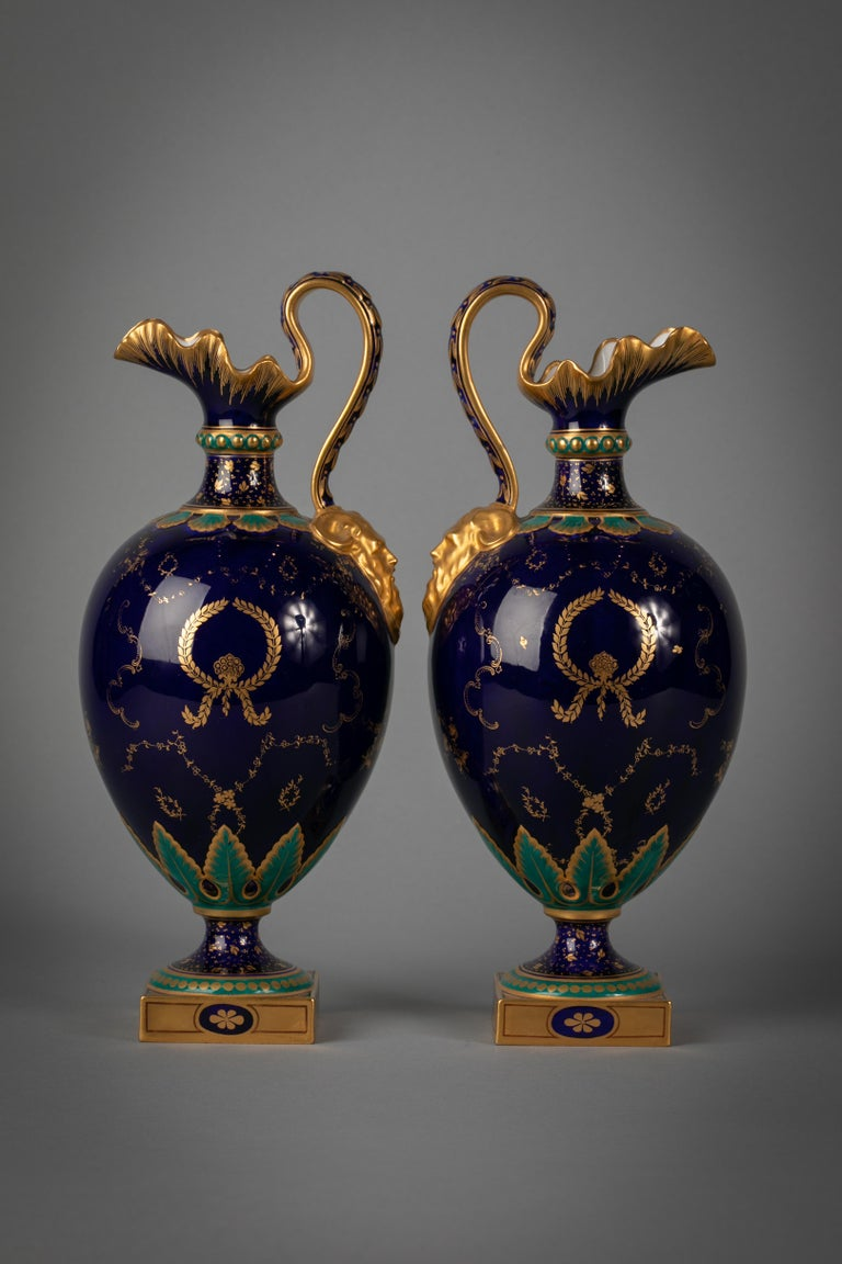 Each with hand painted scenes of exotic birds on a cobalt blue background, with satyr mask handles. Signed Charles Harris. With Royal Crown Derby Mark.