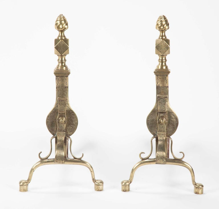 A fine pair of brass andirons with scrolling etched designs. The flame finials over diamond squares above a vase form body held up by cabriole legs is quite elegant. English, early 19th century, Regency period.