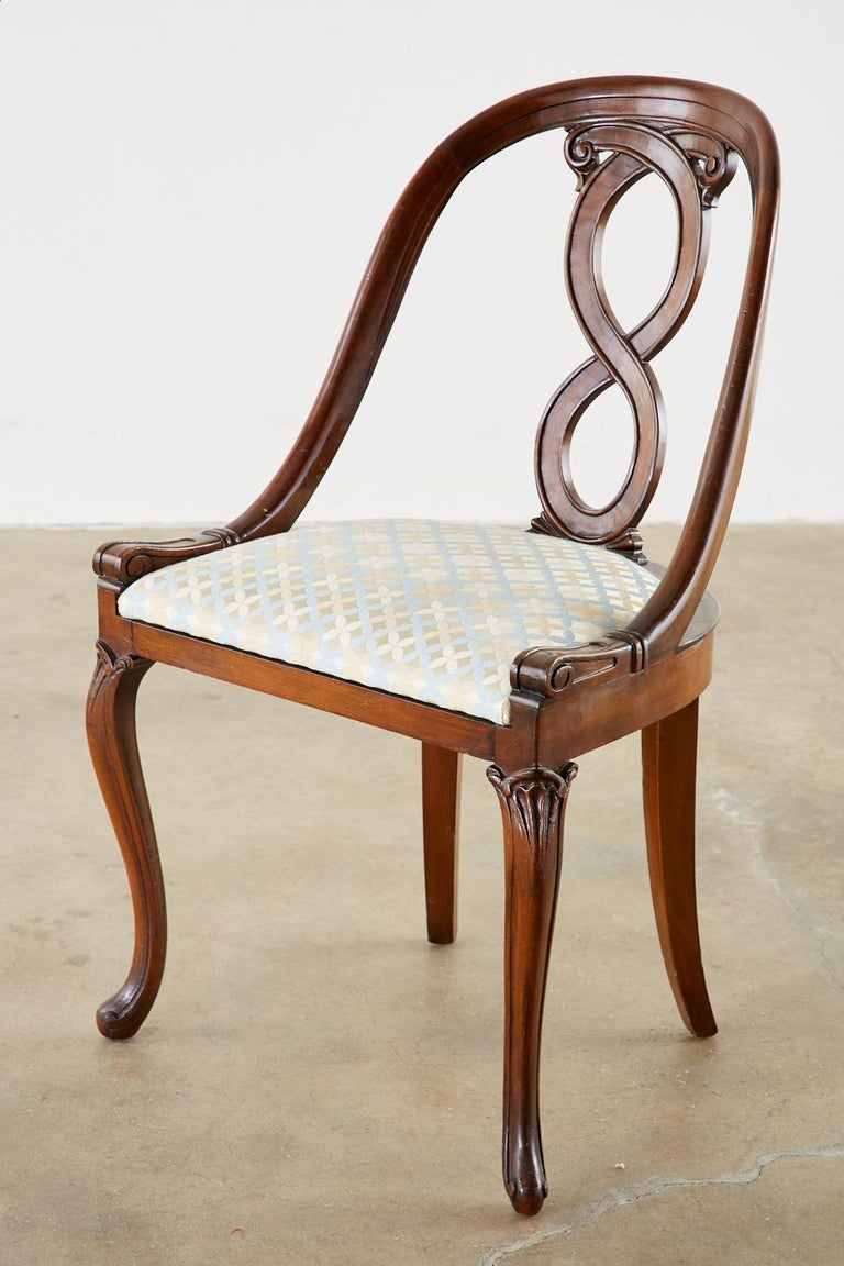 Distinctive pair of English regency chairs featuring a spoon back form. Constructed from mahogany with a carved ribbon design back splat. Supported by graceful cabriole legs in the front. Newer upholstery with a geometric design brocade fabric in a