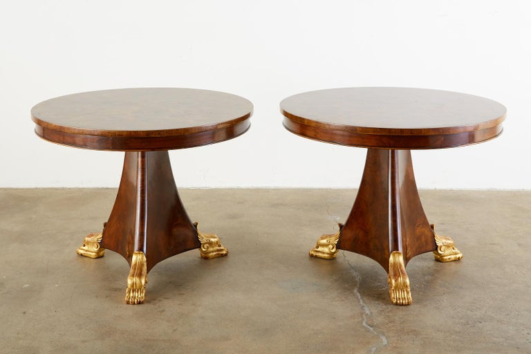 Fine matched pair of English Regency style pedestal tables. Featuring a dramatic burl veneer top. The round tables could serve as center tables, dining tables, or library tables with a 28 inch height. The triangular pedestal flares out on the end