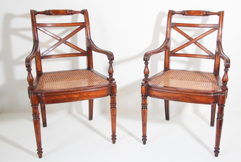 Pair of 20th century English Regency style library armchairs with X-shaped back, turned top rails and arms, and cane seats. Pair of elegant classic armchairs with rounded arms raised on carved feet, solid wood construction, distressed antique