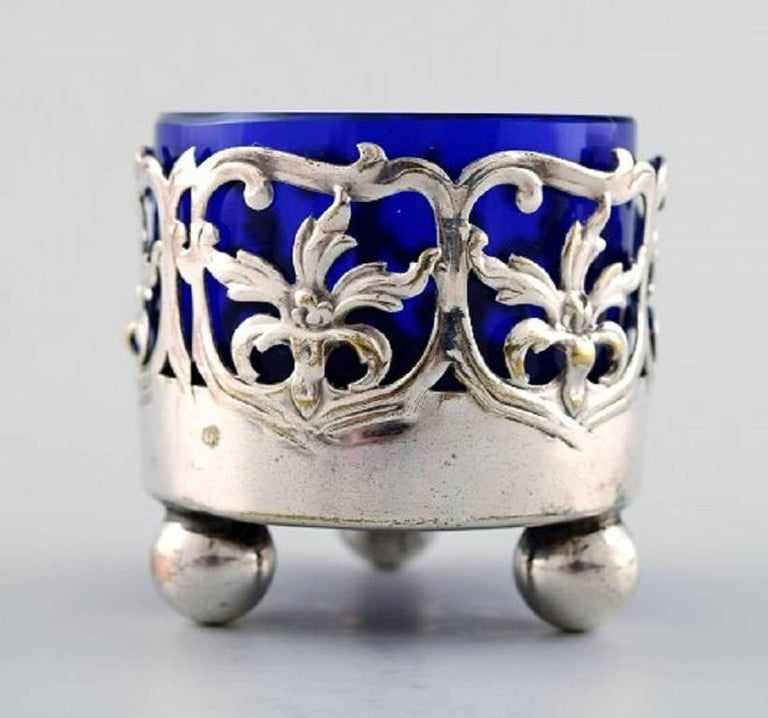 A pair of English salt cellar with glass inserts in blue of English silver plate. Stamped, circa 1900. Measures: 5 cm. x 4.5 cm. In very good condition.