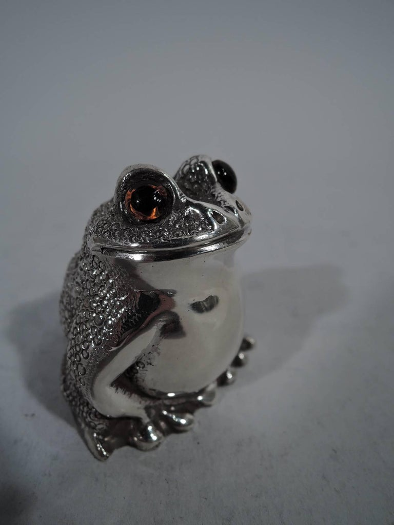 Pair of English sterling silver figural salt and pepper shakers. Each: A squatting reptile with legs gathered close to body. Scaly back, smooth front, and intense glass exophthalmic eyes. Closed mouth set in smirking smile. Plastic plug. London