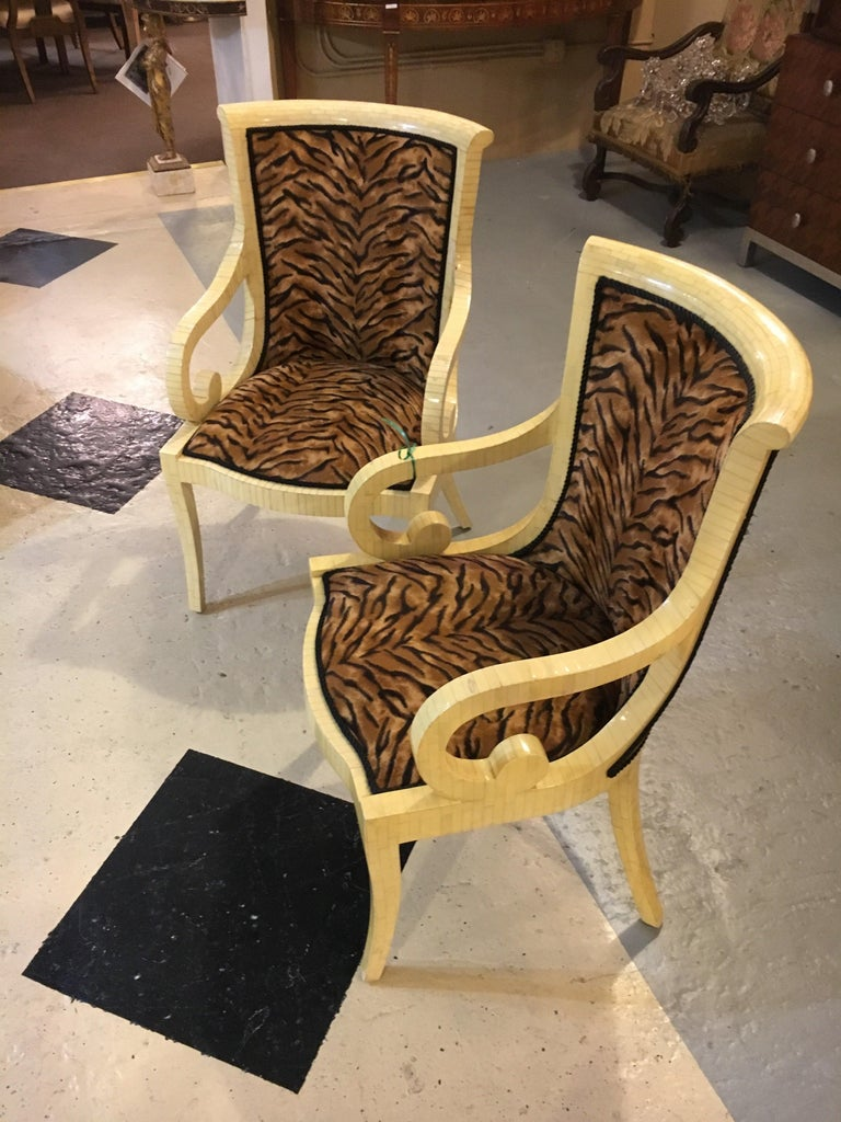 Pair of Enrique Garcel off-white bone style armchairs, signed. Each tessellated form armchair with scrolling arm and body type. Both stylish and sleek showing off a nice leopard upholstery fabric. Having been previously touched up in a professional