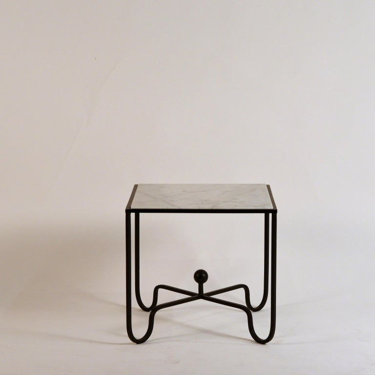 Chic pair of wrought Iron and marble 'Entretoise' side tables by Design Frères. Matte black wrought iron bases with honed white veined marble tops.