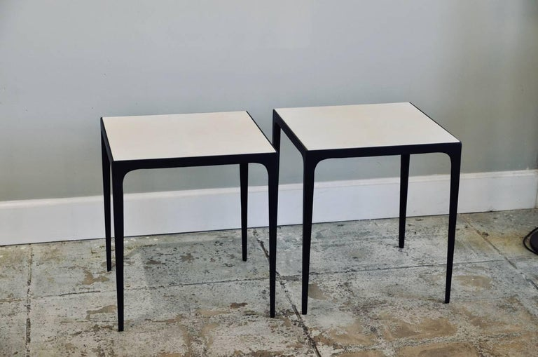 Pair of 'Esquisse' parchment and wrought iron side tables by Design Frères. Beautiful hand-finished parchment tops fitted onto a slender matte black wrought iron base.