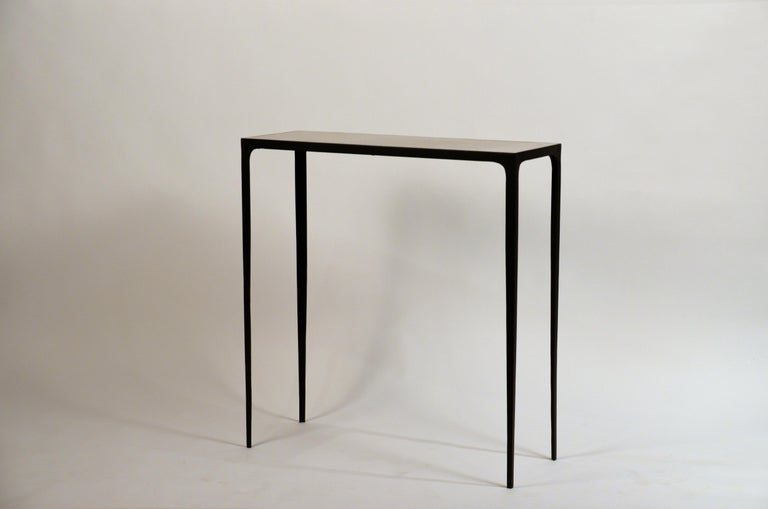 Pair of understated 'Esquisse' wrought iron and parchment consoles by Design Frères. Chic genuine parchment tops fitted onto a slender matte black wrought iron bases.
