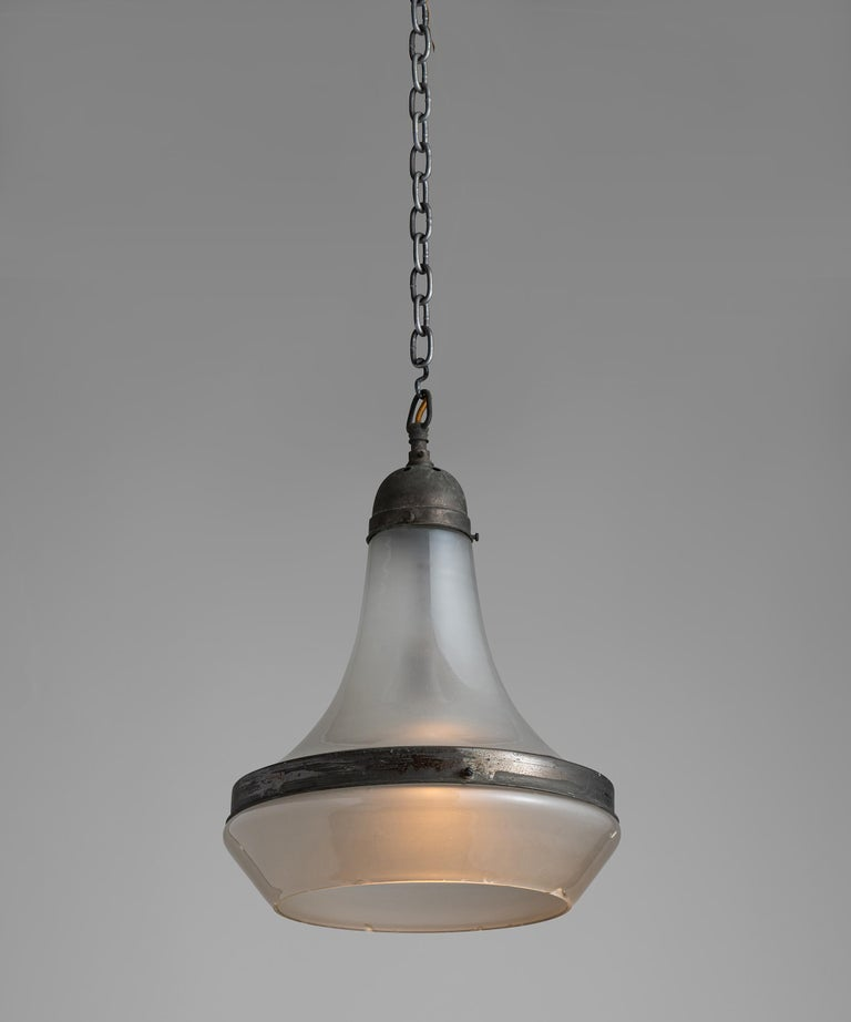 Pair of etched glass pendants  Germany, Circa 1930  Tapered glass upper with lower etched glass open shade, secured with steel binding and gallery with original dark patina.