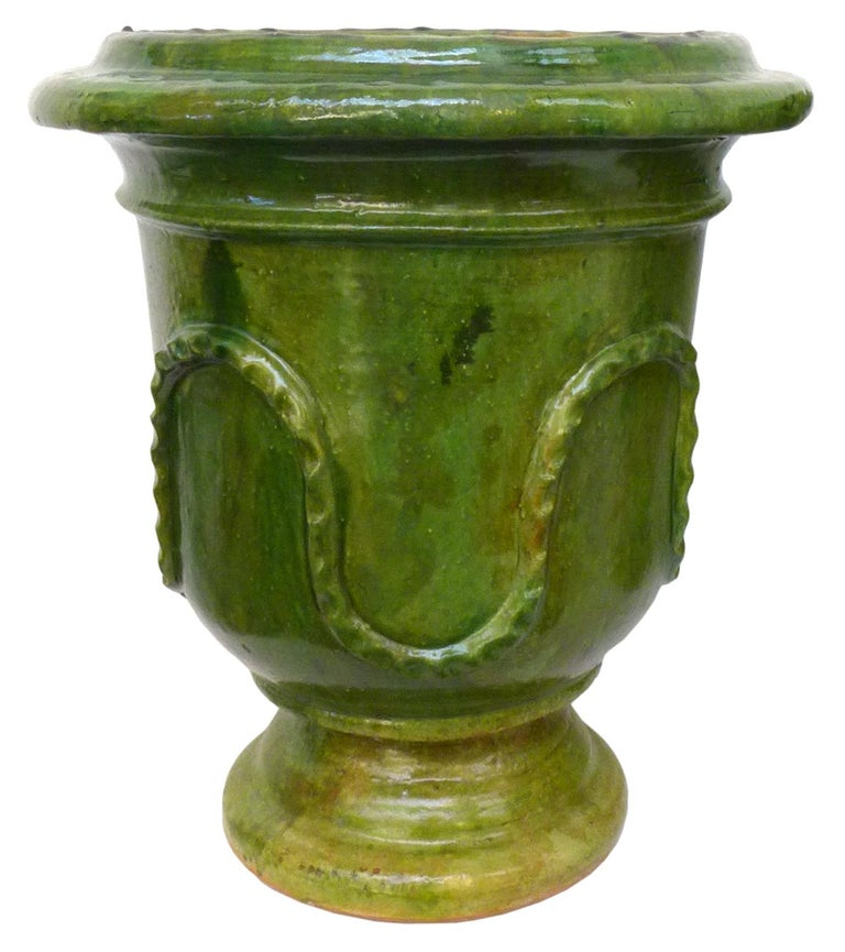 A wonderful pair of vintage European neoclassical glazed terracotta planters. A hand-formed, traditional motif with circling, decorative, undulating ribbon detail and an exterior in variegated green glaze. Elegant botanical elements, great for use