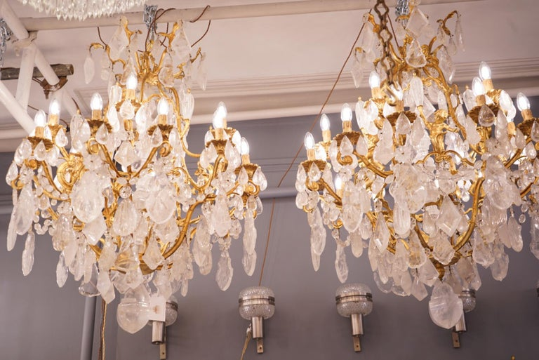 A magnificent pair of French gilt bronze cherub chandeliers. A birdcage design with upper crown and profusely hung with rock crystal large pendants and smaller drops. 6 cherubs each holding a rock crystal torch. Terminating below with a carved rock