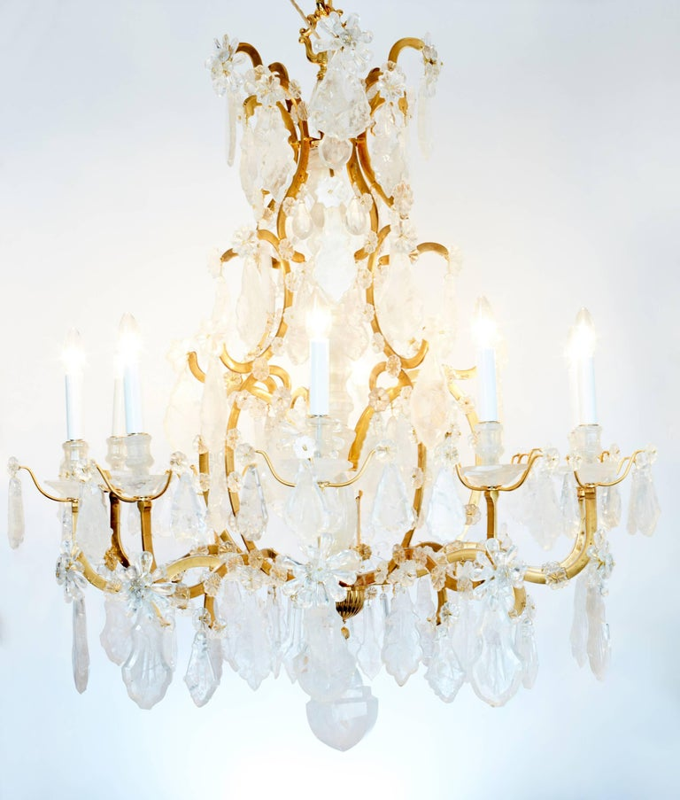 Pair of beautiful French ten-light chandeliers in the Louis XV style. The bronze frame is profusely covered with rock crystal rosettes. The arms are hung with large rock crystal drops topped with rock crystal flowers. Terminating below with a large