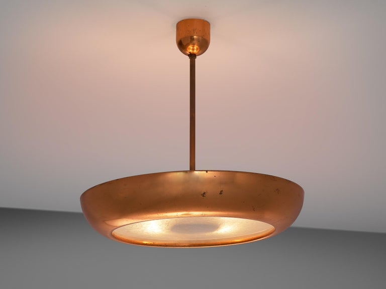 Large pendants, copper and glass, Europe, 1970s.  This very large copper pendant is very sleek and organic at the same time. The lamp is Minimalist in the sense that there is no ornate decoration or additional details. The shade, which is shaped
