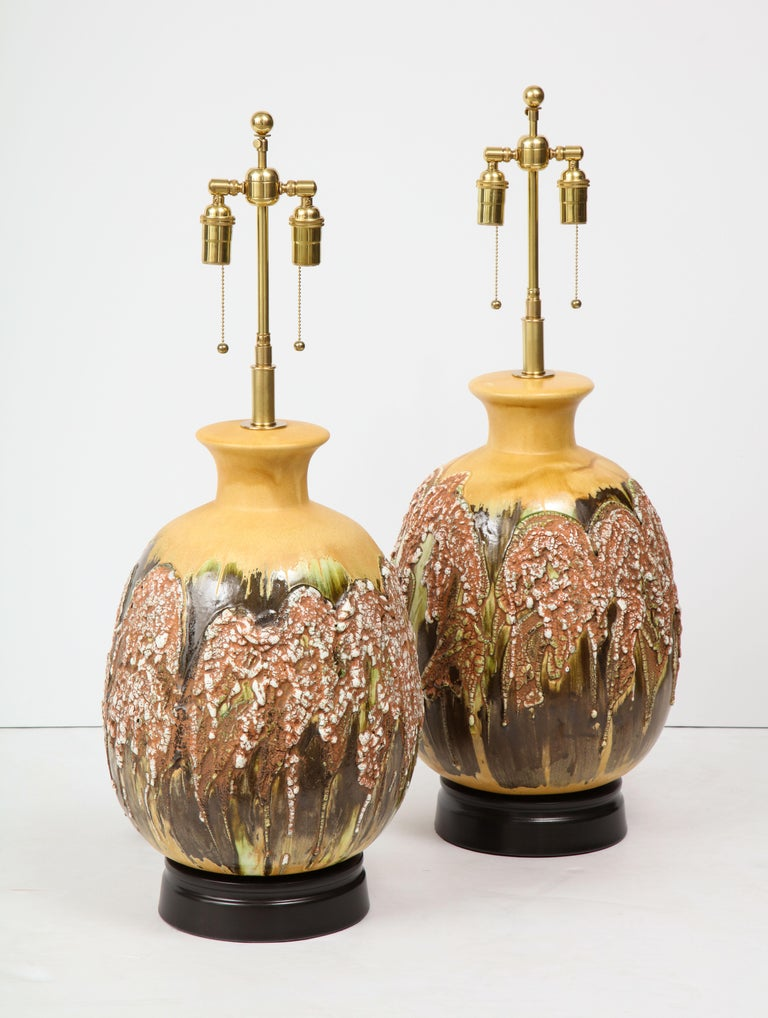 Wonderful pair of extra large Italian ceramic lamps with a beautiful textured Volcanic glazed finish. The lamps have been newly rewired for the US with polished brass double clusters.