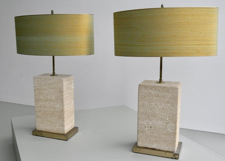 Pair of extra large sandstone, brass and silk table lamps by Roger Vanhevel. The shades from the pair are newly upholstered in gold/yellow thread silk. Very large and heavy pieces, these lights are dimmable and adjustable in height.