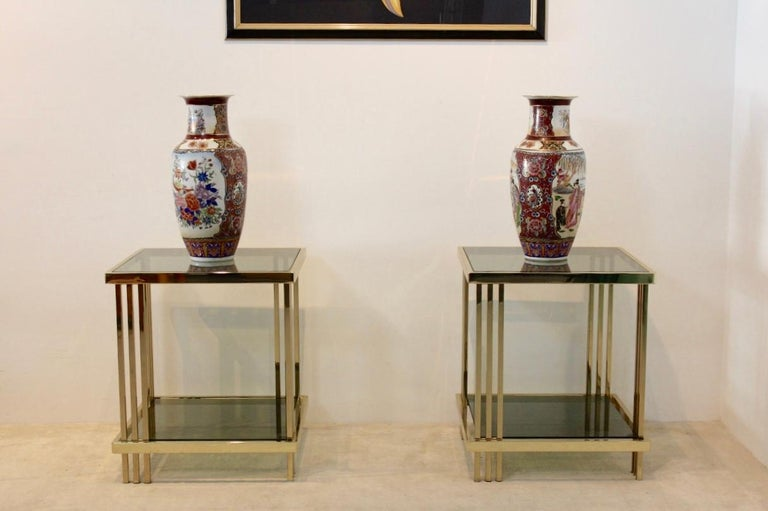 Sophisticated set of French side tables with a stunning brass frame with a beautiful graphical design. The solid and glossy square shaped tables with beautiful Brass accents has two tier green smoked glass. The tables are a unique example of the