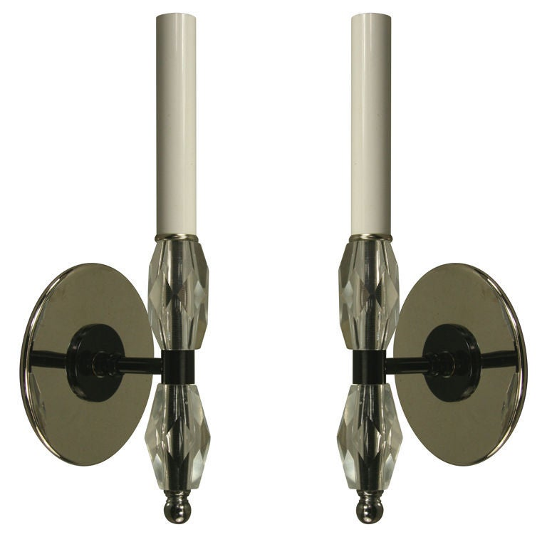 #2-418 a pair of faceted crystal single light arm over a black and nickel backplate.