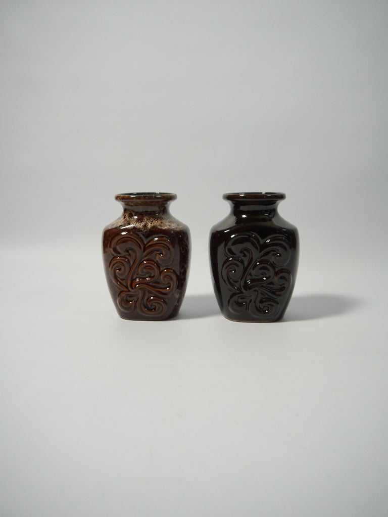 Pair of German pottery vases fabricated by Strehla former East Germany in the 1960s. One vase deep black glaze, the other in a speckled brown glaze, but both identical in dimension, shape and organic floral pattern.