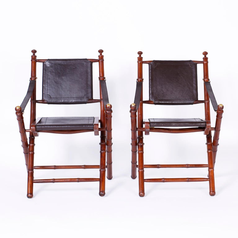 Pair of midcentury folding faux bamboo chairs expertly crafted in mahogany with brass hardware and soft leather backs, seats, and strap arms.