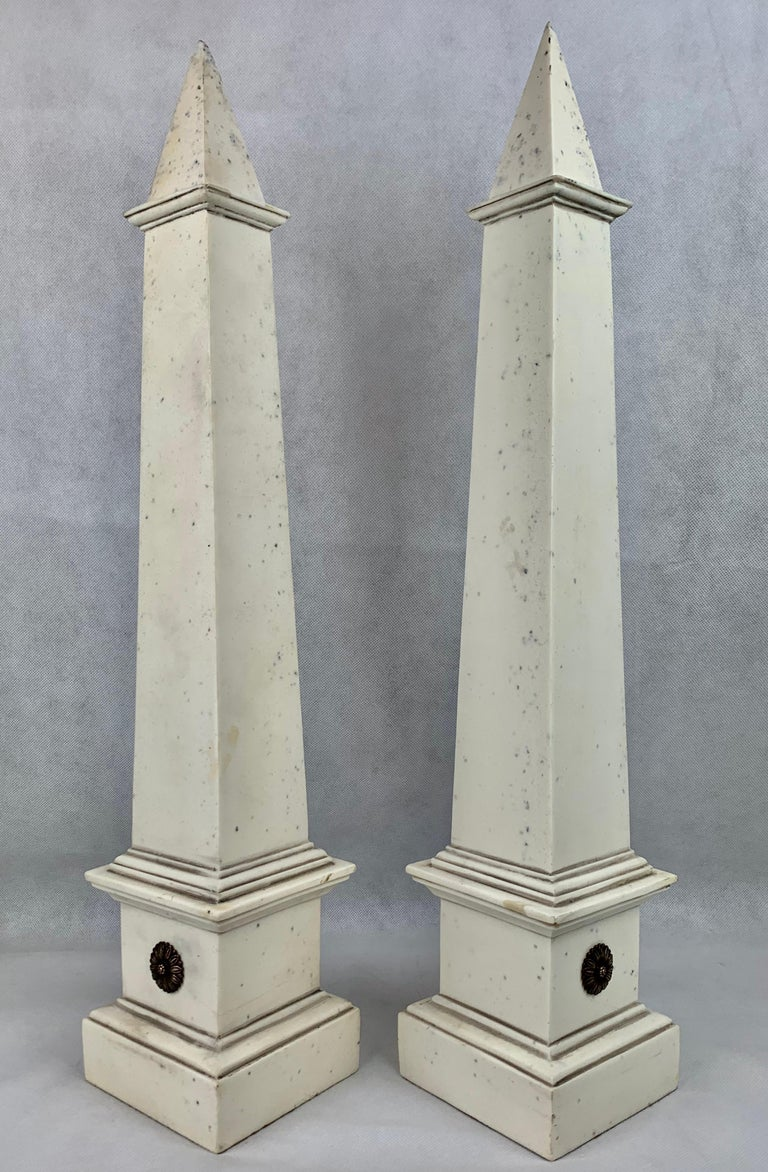 Pair of stunning tall faux ivoire neoclassical obelisks. Edited design with each obelisk have a single pair of gilt marguerite flowers for ornamentation. The tip of each obelisk has a bit of roughness. Measures: Height-23.5