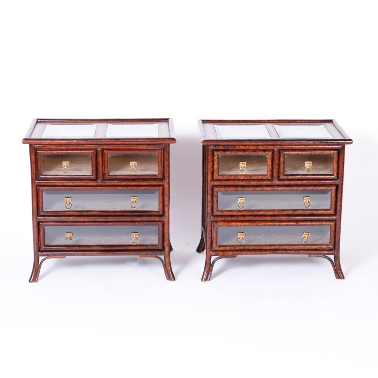 British colonial style stands with faux tortoise bamboo frames and tooled leather panels on the sides and back, featuring bevelled glass panes on the top and four drawer fronts. The drawers are lined with marbleized book paper and have brass lion's