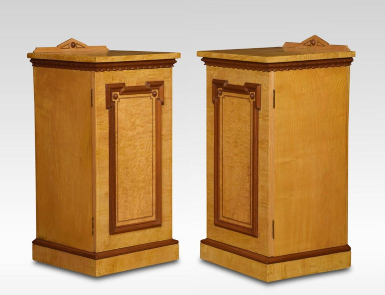 A pair of ash bedside cabinets having architectural raised back to the square top above carved mahogany freeze the door opening to reveal a single drawer and shelf. All raised up on plinth base. (adapted) Dimensions Height 33 inches Length 16