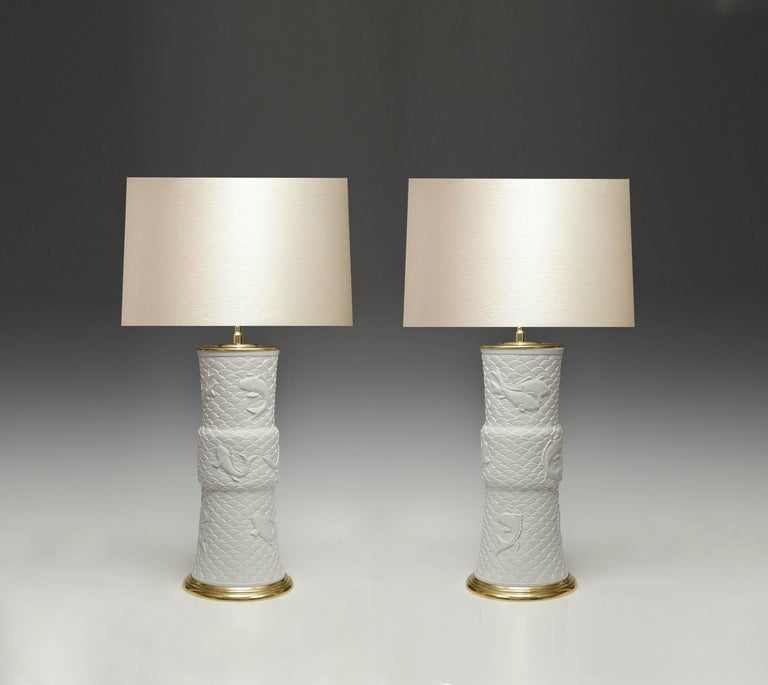 Pair of fine carved off white porcelain lamps with fishes swim in stylish waves decorations.