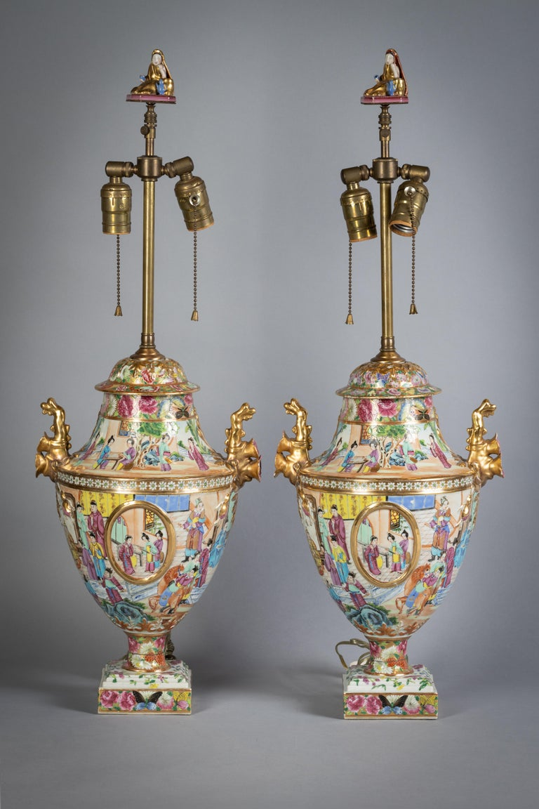 Finely and delicately enameled with figures in various settings, each side with molded gilt cartouche with further miniature scenes, the gilt handles with flowers, the base similarly decorated with flowers and butterflies, the original finials now