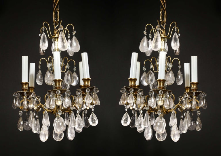 A pair of continental Louis XVI style bronze and rock crystal multi light triple tier chandeliers embellished with cut rock crystal prisms.