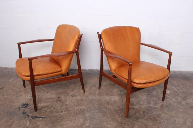 A pair of walnut delegate armchairs designed by Finn Juhl for Baker. Fully restored and upholstered in waxed leather.