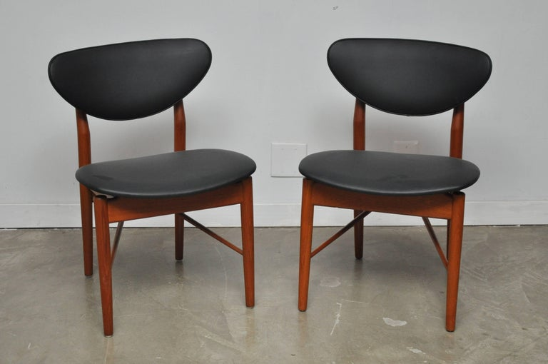 Pair of Finn Juhl NV 55 dining chairs designed in 1955 and produced by Niels Vodder. Fully restored teak and brass frames, with newly upholstered black leather cushions.