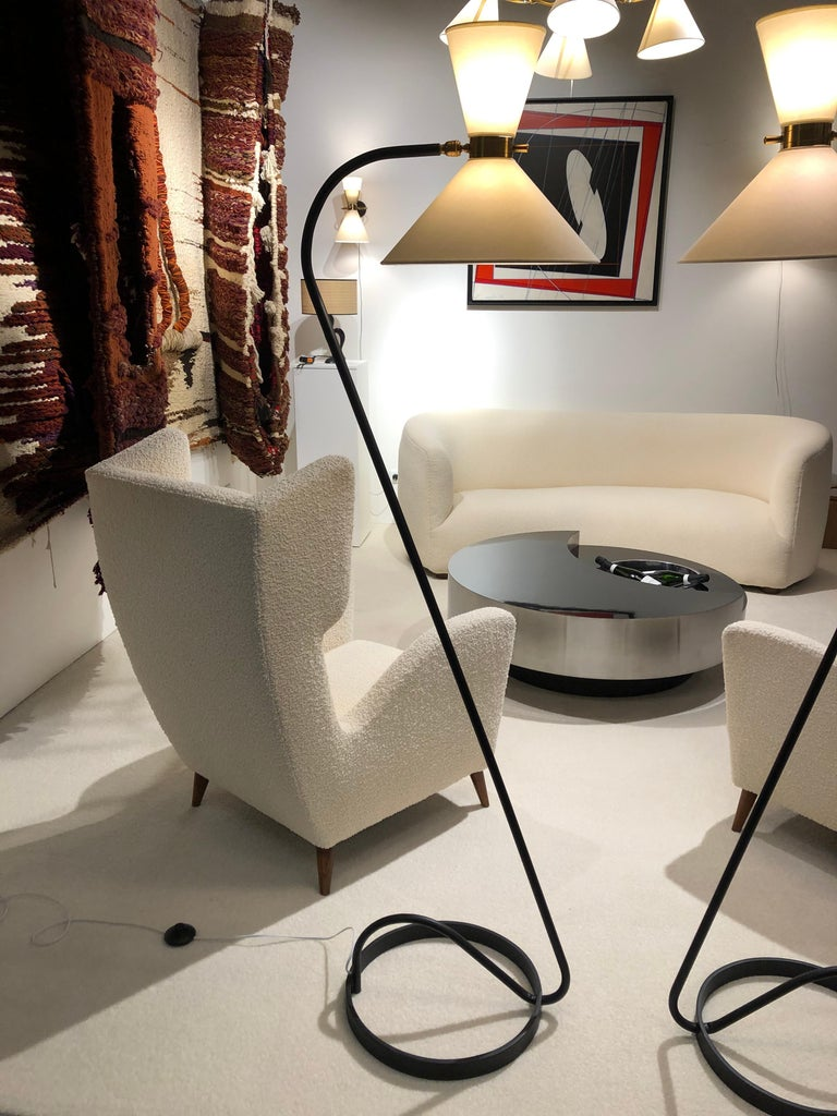 Pair of floor lamp in black lacquered metal and brass, composed of a circular base in black lacquered, a brass ring articulated by a ball joint, receiving on both sides two conical lampshades diffusing light. A brass handle allows easy