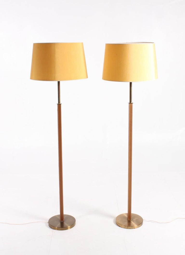 Pair of floor lamps covered in patinated leather on a round brass base. Designed and made in Sweden in the 1950s. Original condition.