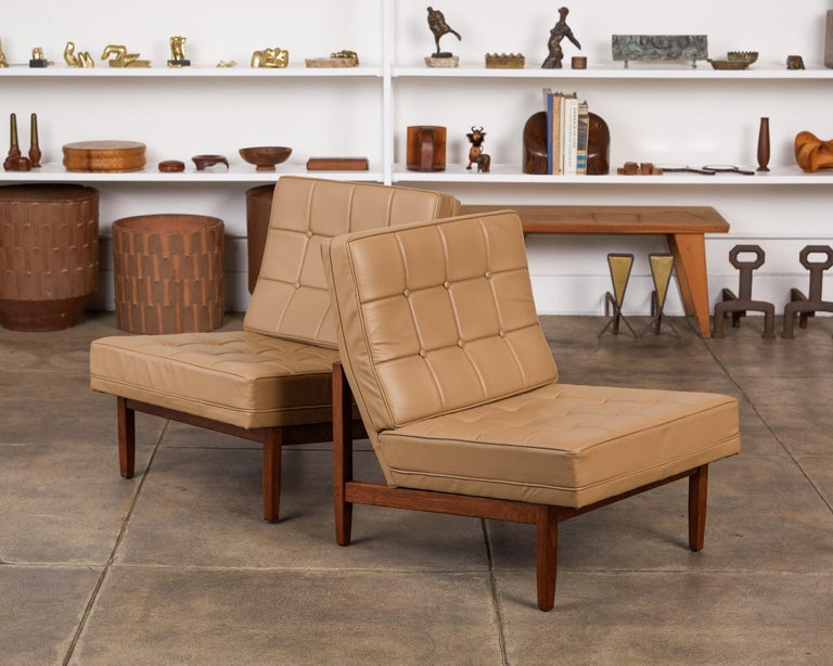 Pair of slipper lounge chairs by Florence Knoll, USA, circa 1950s. The chairs feature a walnut frame with attached tufted leather back and seat cushions. A Classic design by one of the matriarchs of American Modernist furniture