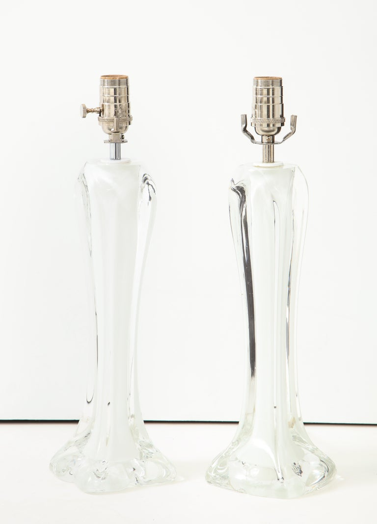 A lovely and graceful pair of white glass lamps made my Flygsfors, Sweden. The silhouette of the lamps is tapered, with a base resembling petals in a flower. This pair is sculptural, and are not only beautiful lamps, but works of art! The height