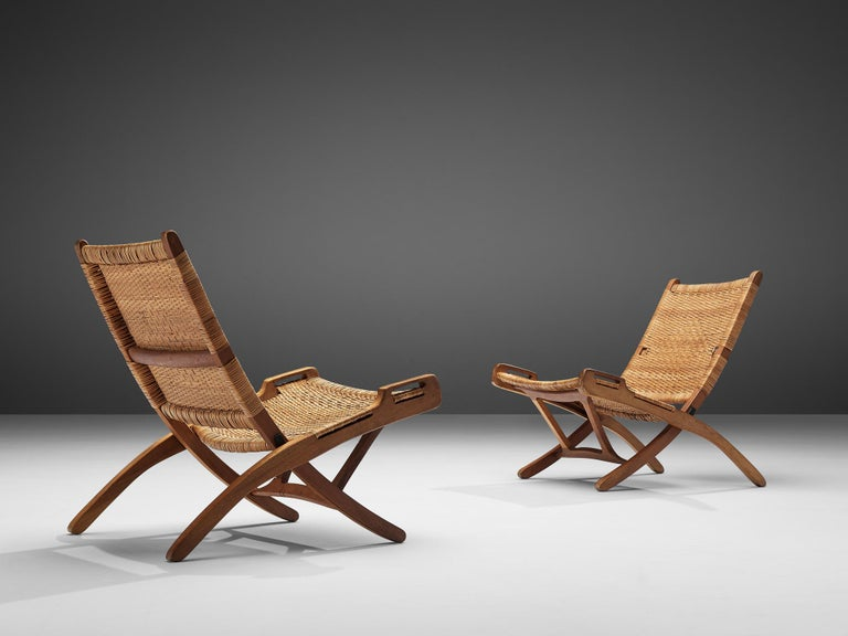 Pair of folding chairs, wicker, teak, Denmark, 1960s.  A foldable and portable chair with a natural appearance. The chair features a beautiful detailed wicker backrest and seating making the low position not only comfortable but also worth seeing