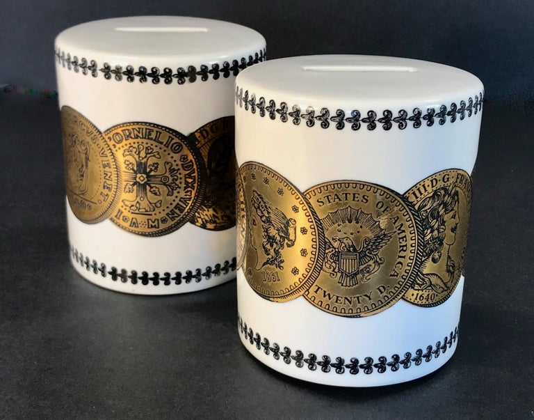 A pair of white porcelain coin or piggy banks designed by Piero Fornasetti for Neiman Marcus. Gilt coin motif with scrollwork detailing at top and bottom. These retain the original stoppers and we have added cork stoppers. Coin banks by Fornasetti