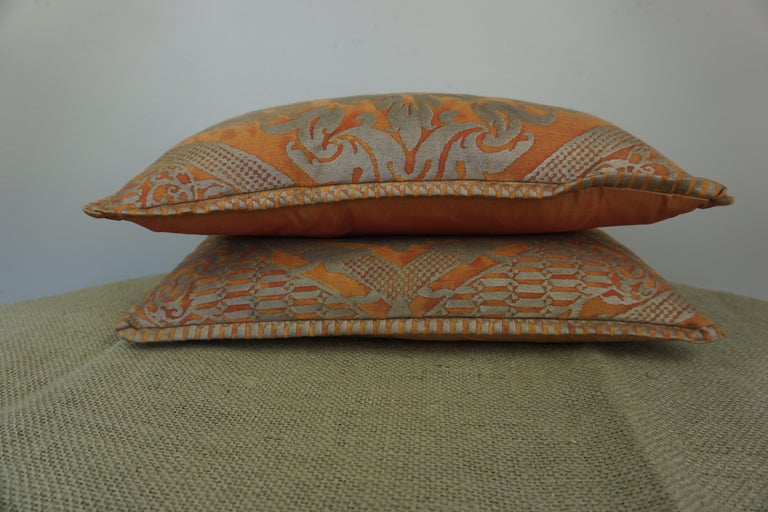 Pair of custom accent pillows made with bittersweet & silvery gold colored cotton Fortuny fronts and vibrant silk backs. Down inserts, zipper closures.