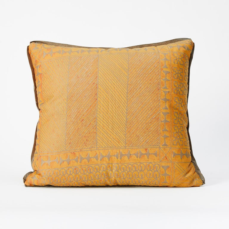A pair of Fortuny fabric cushions in the Ashanti pattern, gold and silver color way with silk edging. Gold wool fabric with brushed texture backing. The pattern, a Geometric design with African tribal motif. 