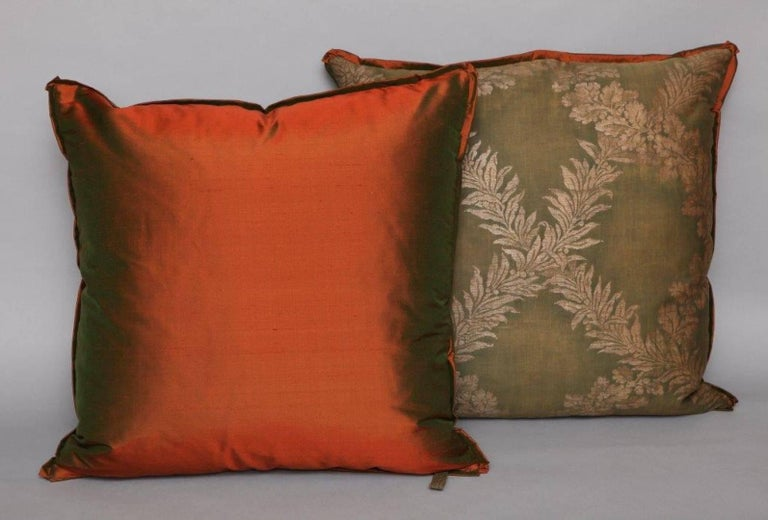 A pair of Fortuny fabric cushions in the Crosoni pattern, green ground with silk bias edging and red taffeta backing material, the pattern, an 18th century French Empire design with formal motif. Newly made using vintage Fortuny fabric, discontinued