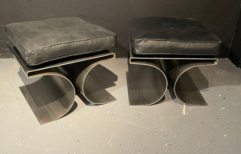Pair of François Monnet attributed Benches in a brushed stainless steel with a black leather cushion. These impressive Mid-Century Modern benches are simply stunning. The strong heavy and sturdy bases having the typical Monnet form with a flat top