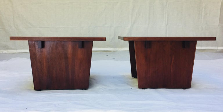 A pair of side tables by California Modern furniture craftsman Frank Rohloff.  The table tops are black resin with pieces of walnut veneer set in the black resin creating an interesting juxtaposition of materials bordered by a walnut outer edge. The