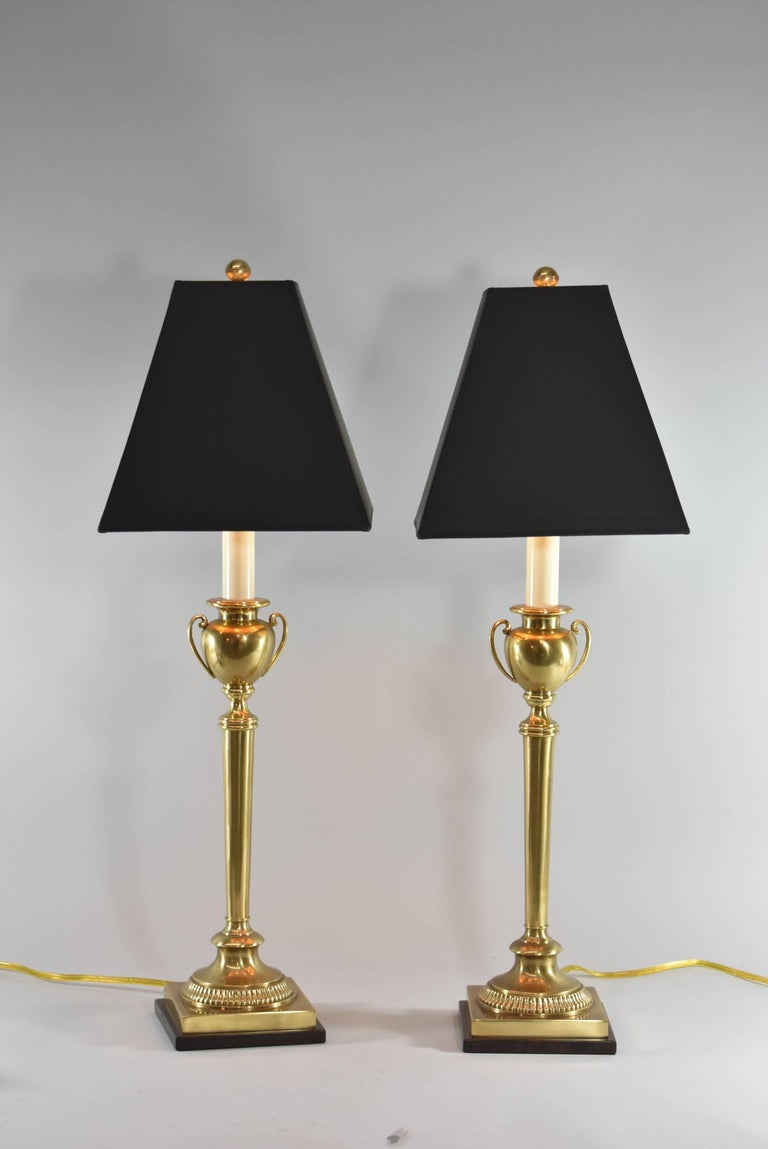 A very attractive pair of table lamps by Frederick Cooper. They feature a slender brass base with an urn form centre and a bronze colored metal base. The dimensions are 30