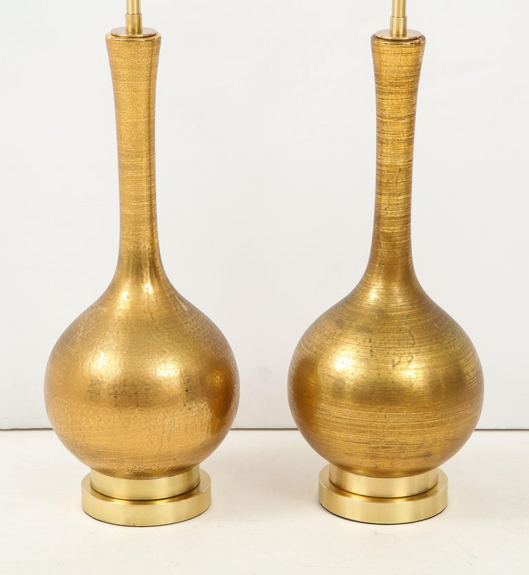 Pair of gold ceramic lamps with a beautiful crackle glazed finish. The lamps are mounted on double stacked brass bases and they have been newly rewired with polished brass double clusters. There are a couple of minor glaze imperfections consistent