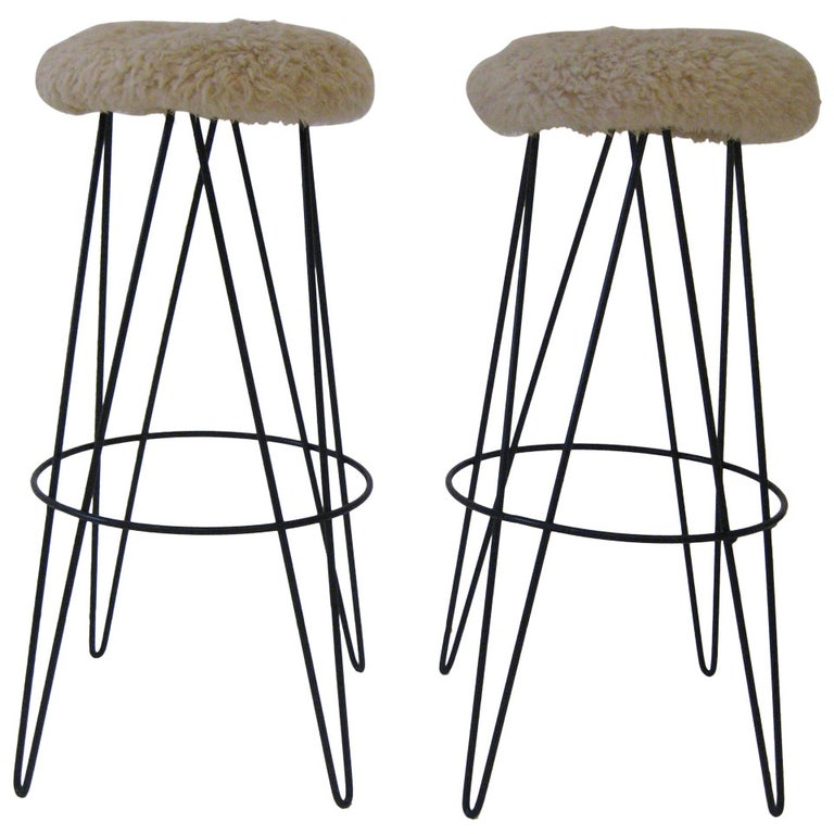 Enameled iron butterfly hairpin legs with sheepskin seats.