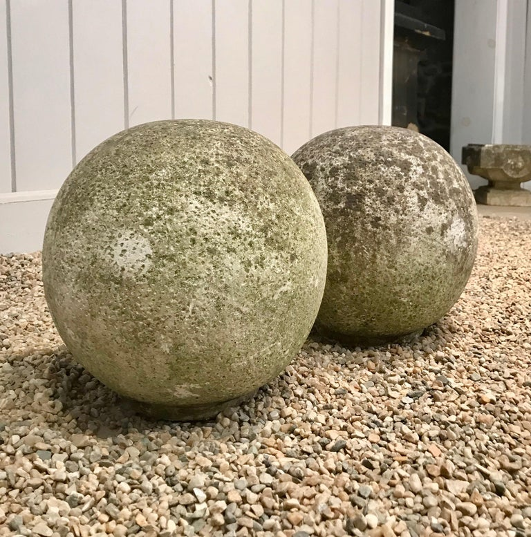 We love these cast stone balls for their stunning weathered surface with moss that will green up if placed in a damp and shady location. In very good vintage condition, with flat bottoms to prevent rolling, they would be wonderful flanking the