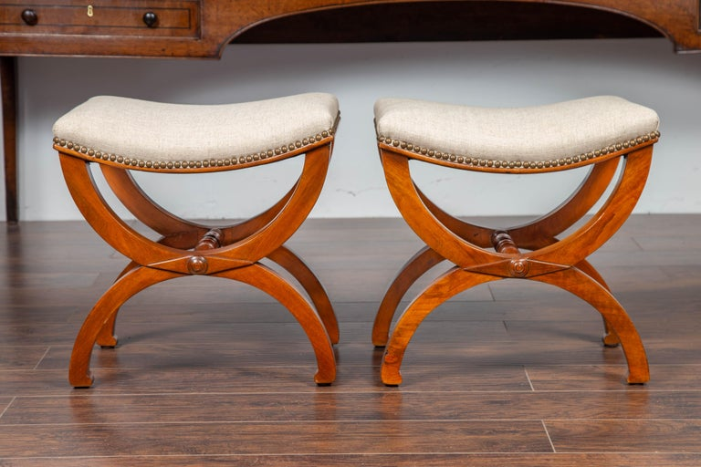 A pair of French Empire style Curule walnut tabourets stools from the late 19th century, with new upholstery and nailhead trim. Born in France during the last quarter of the 19th century, each of this pair of French stools features a rectangular